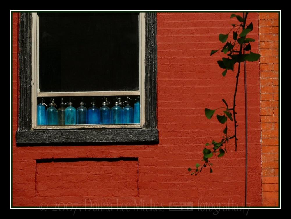 Blue seltzer bottles in window of brick building.