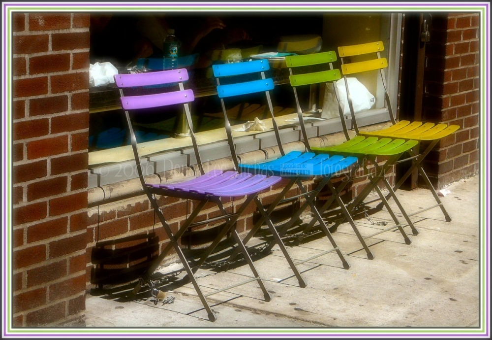 Multi-colour set of chairs outside a deli on 24th.