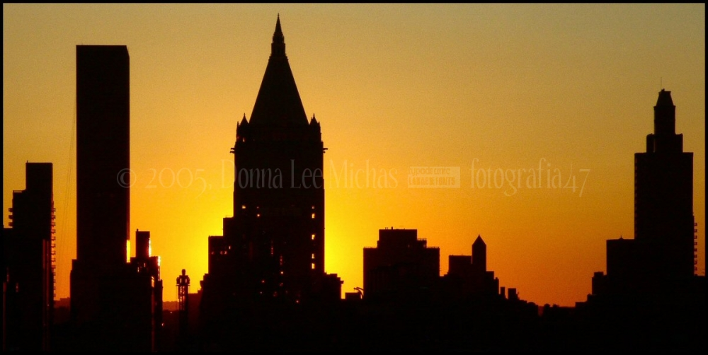 Silhouette of buildings against strong sunset.