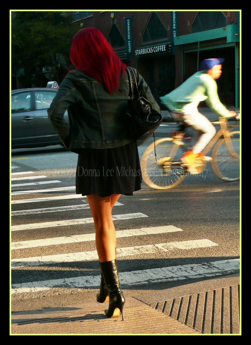 Long-legged, red-haired woman crossing USQE.