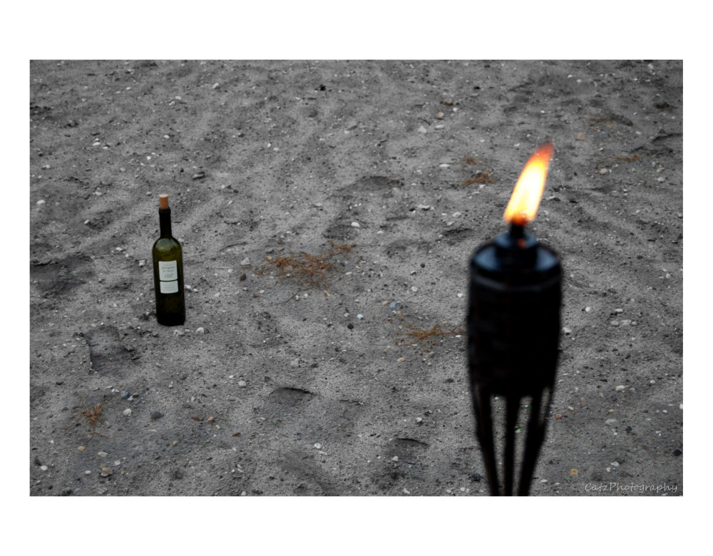 ...Empty Wine Bottle, Sand, and a Tiki Torch...