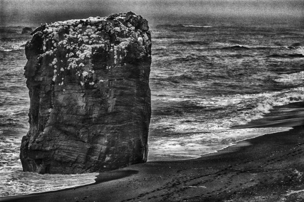 Black stack on a shore line.