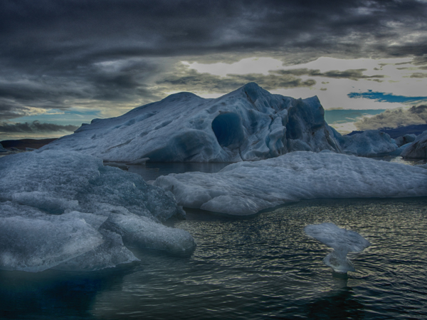 An iceberg cave drifts past on the current.