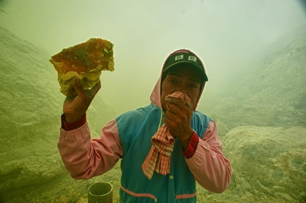 Holding a sizable piece of sulphur.