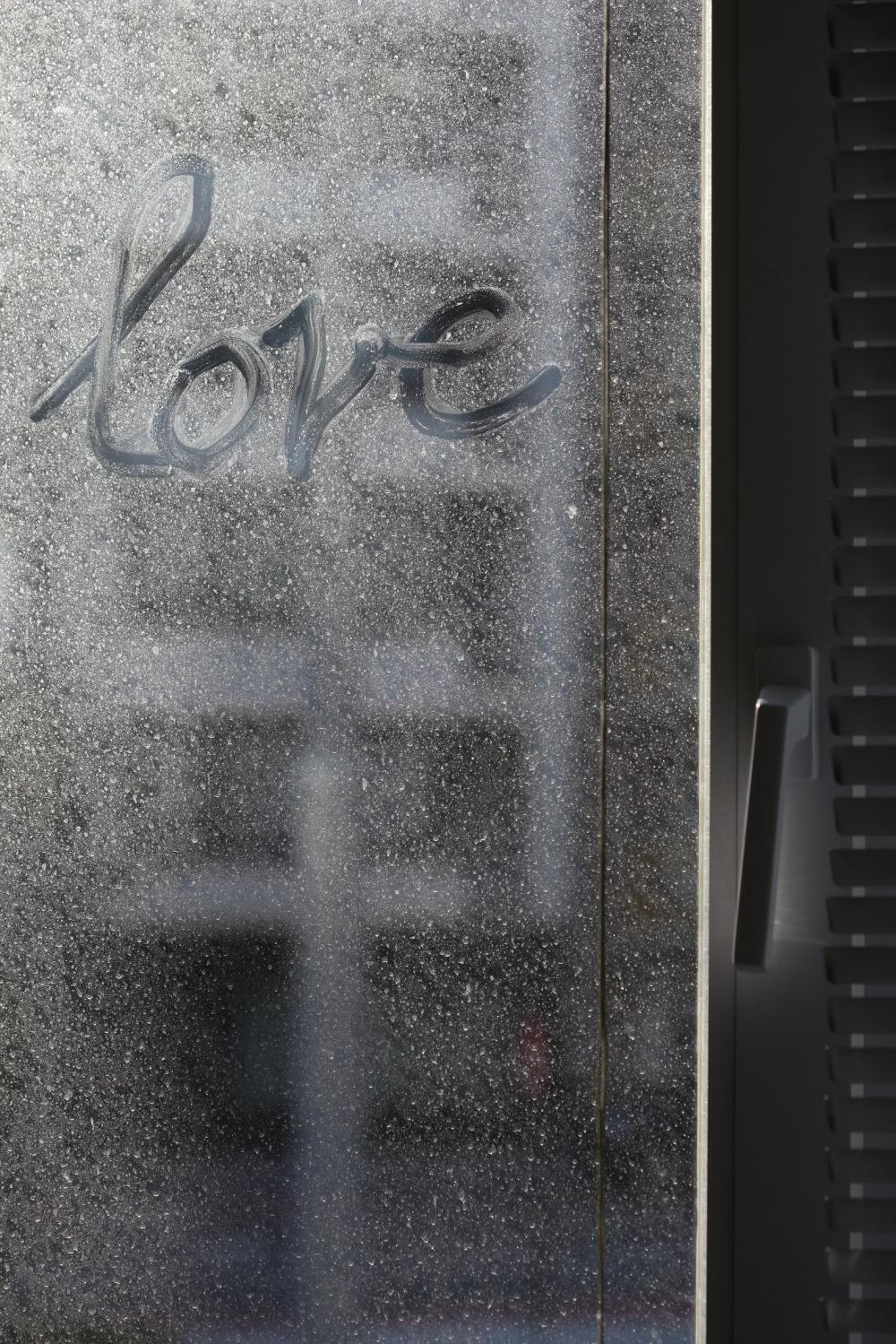 Color photograph of Love on a dusty window...