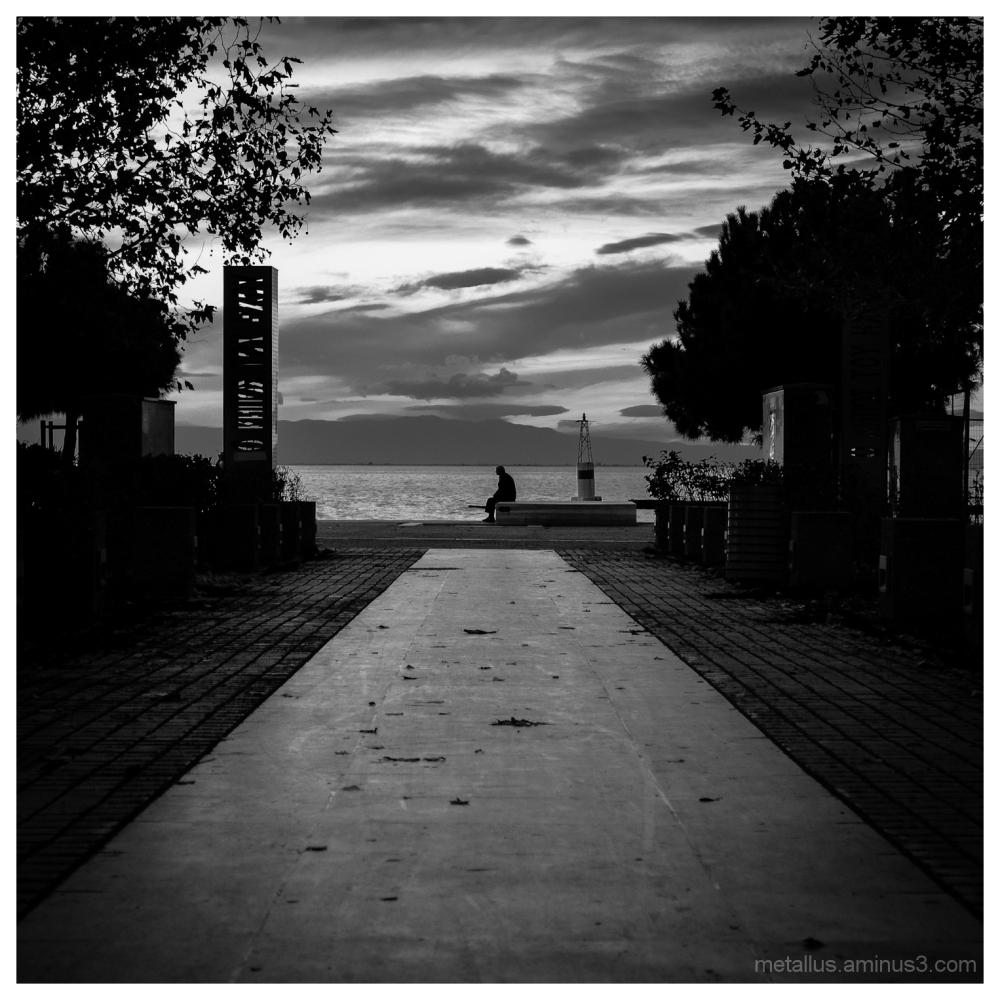 A man sits at Thessaloniki coast boardwalk