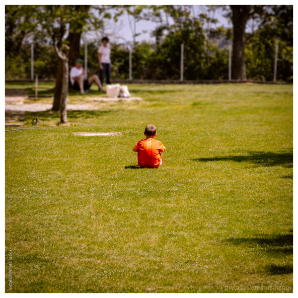 A child in the middle of a green field
