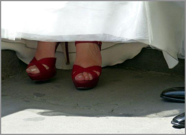 Les pieds de la mariée chaussés de rouge
