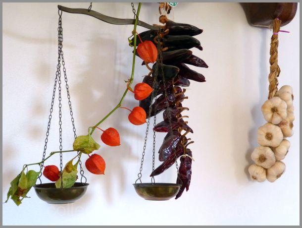 Des piments rouges accrochés au mur blanc ...