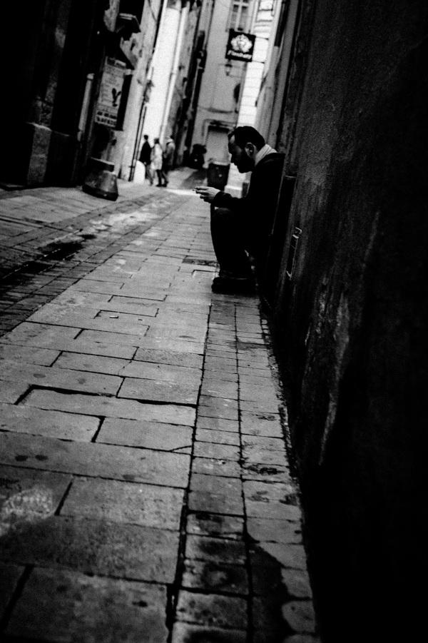 Man sitting in doorway smoking.