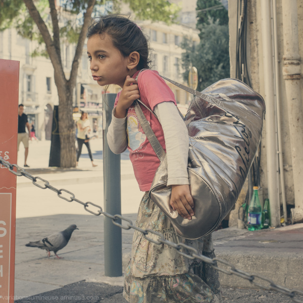 Young gypsy girl with a bag on the street.