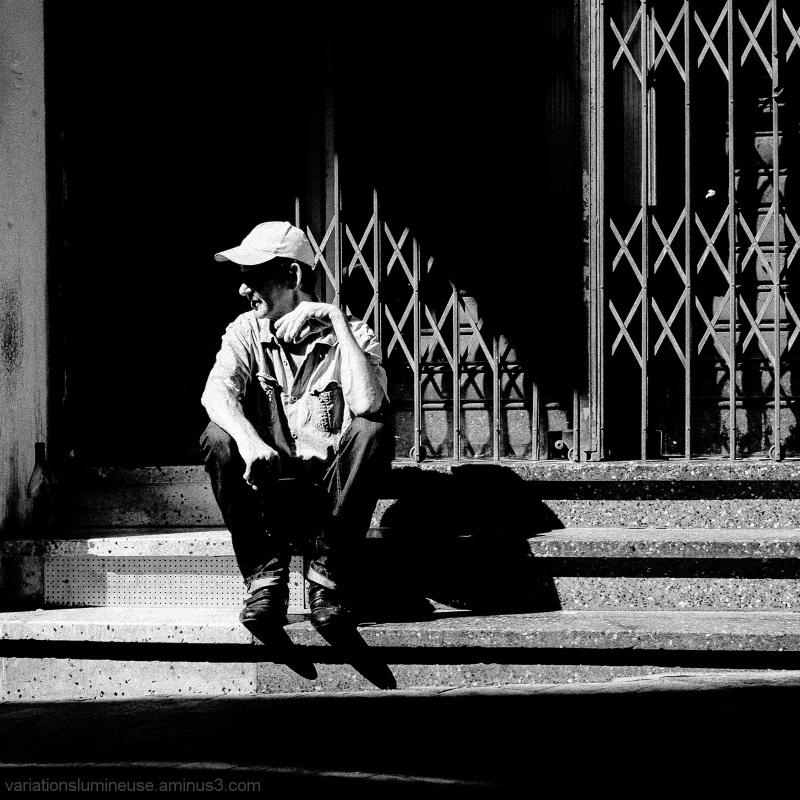 Homeless man sitting on step near bottle of wine.
