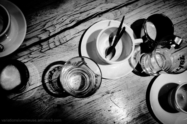 Still-life of cafe table with mugs, milk, water.