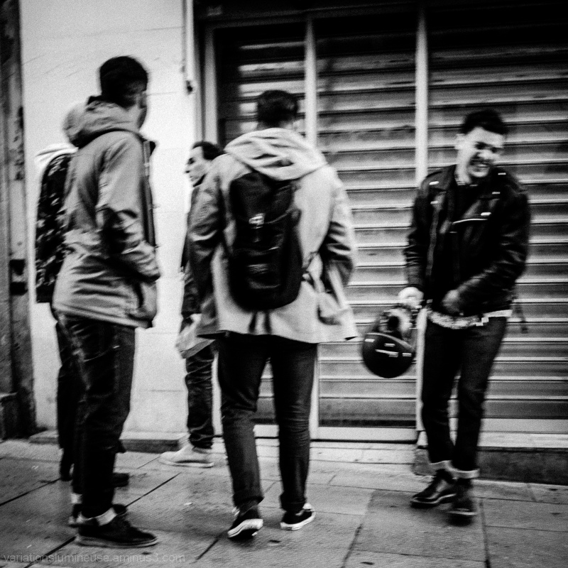 Group of men on street. One laughing.