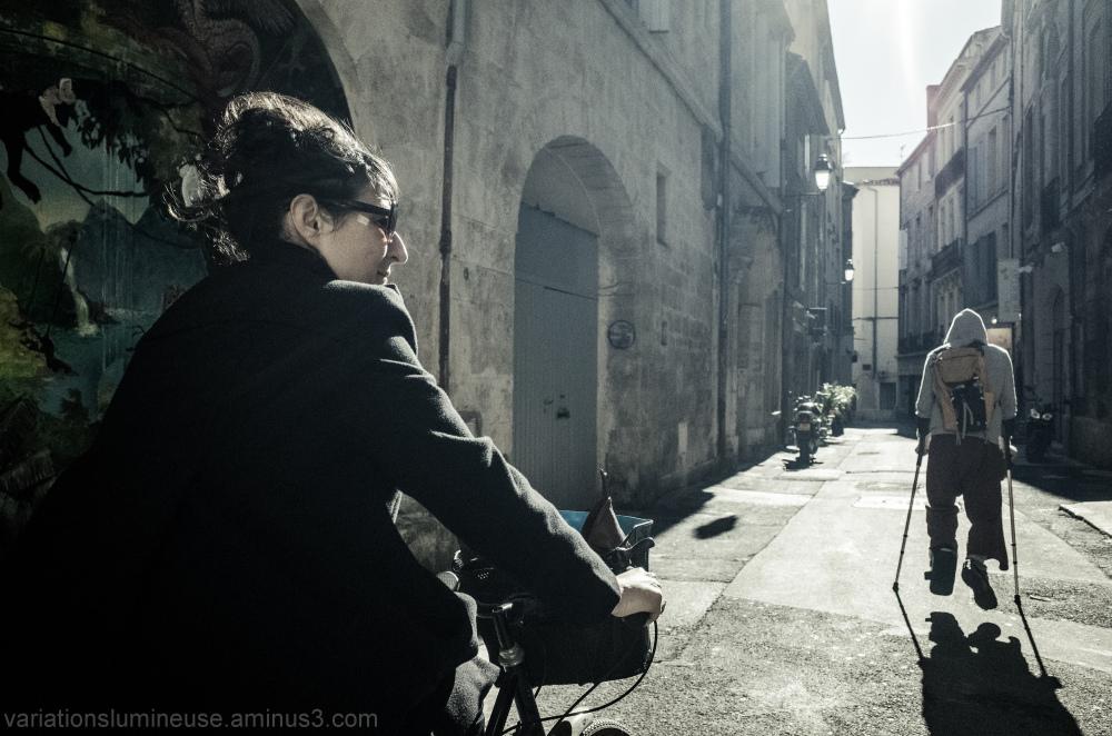 Woman riding, man on crutches.