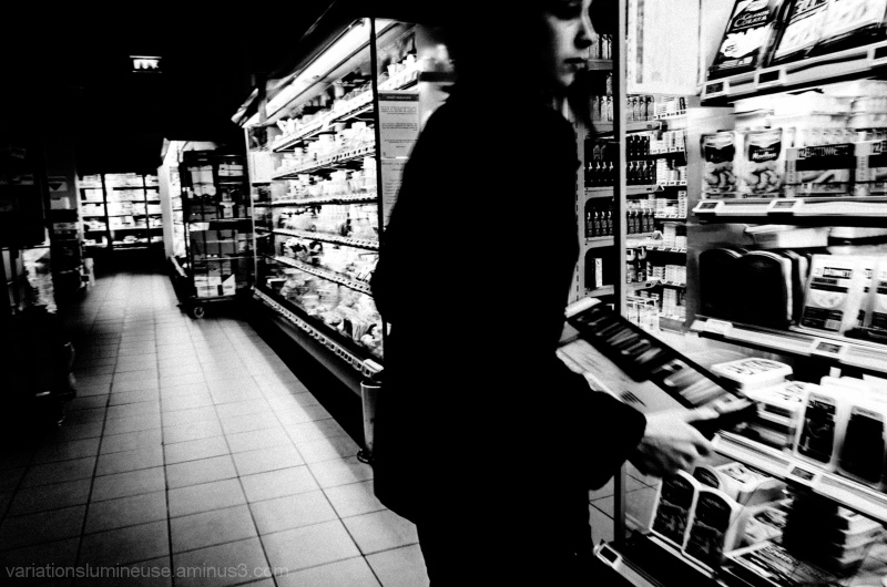 Young woman stocking shelves in supermarket.