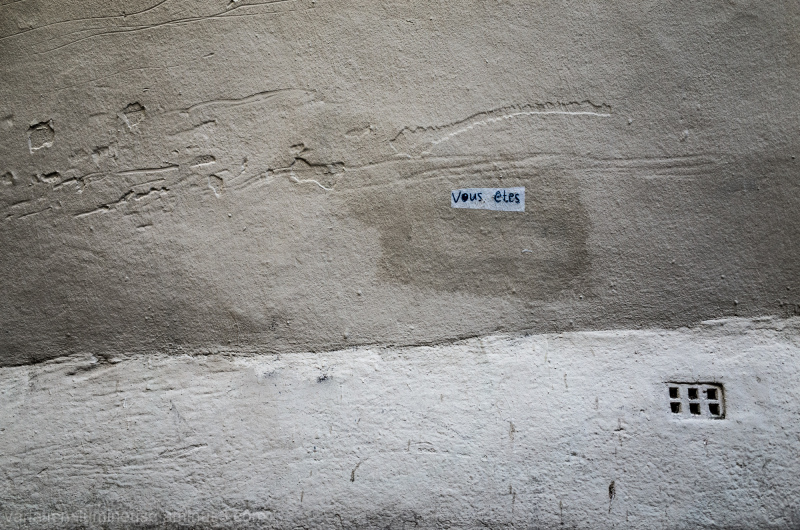Vous etes scrawled on paper stuck on a wall.