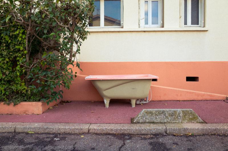 Pink bathtub on the sidewalk.