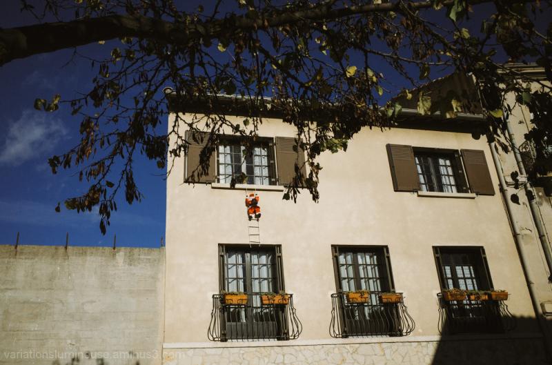 Santa climbing up side of house.