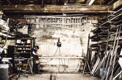 Man working metal in his shop.
