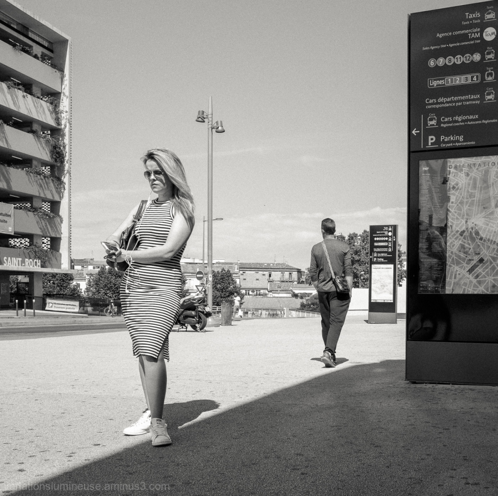Woman waiting outside Montpellier train station.