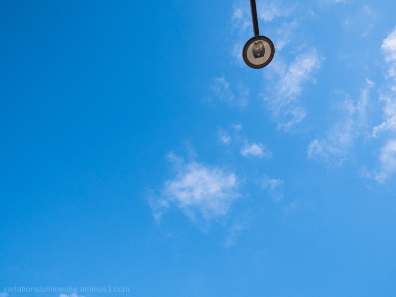Blue sky with clouds and street lamp.