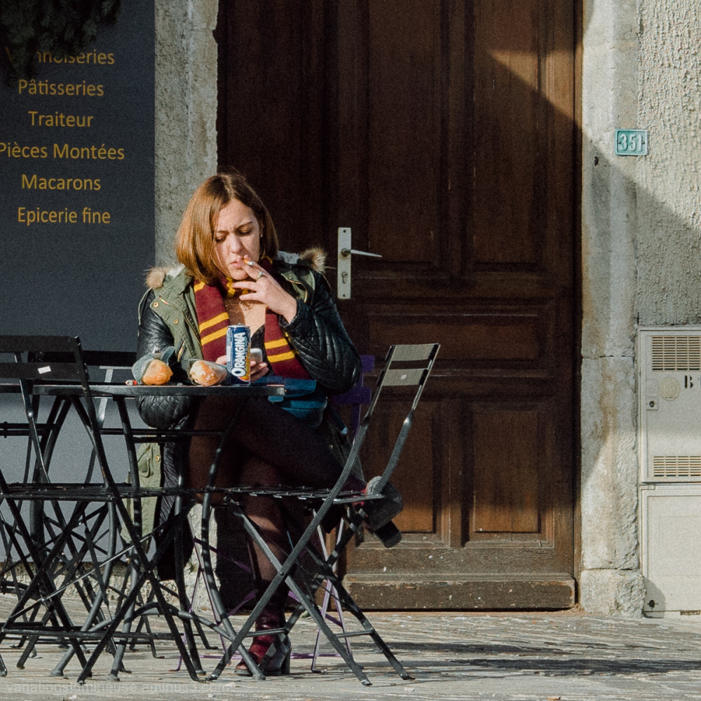 Young woman smoking outside a bakery in France.