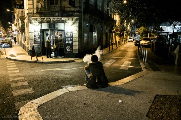 Man sitting on sidewalk smoking.