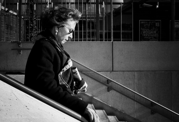 Woman descending stairs at the train station.