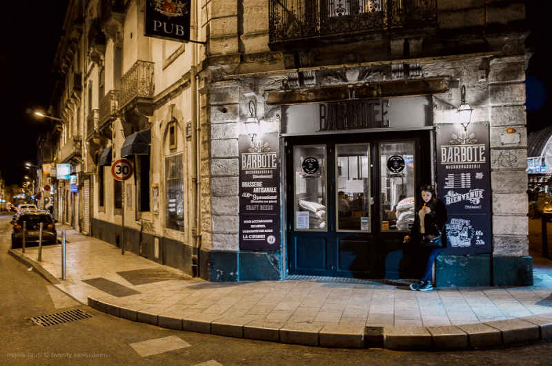Woman outside a pub at night. France.