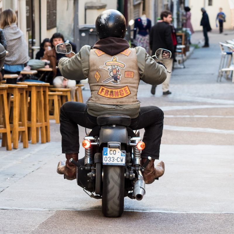 Riding his motorcycle in town.