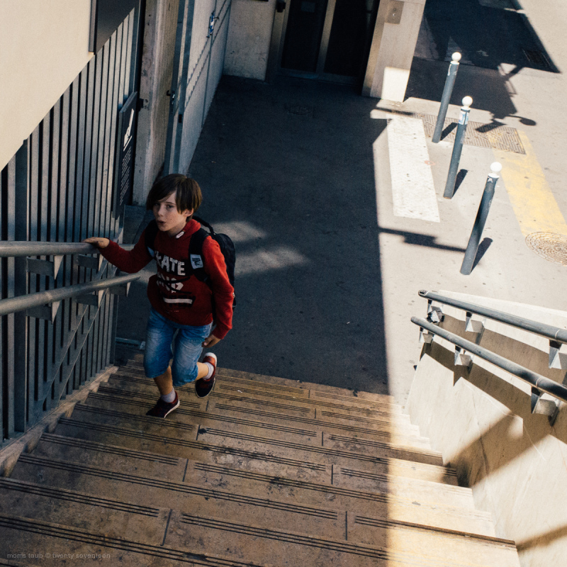 Boy headed up stairs behind train station.