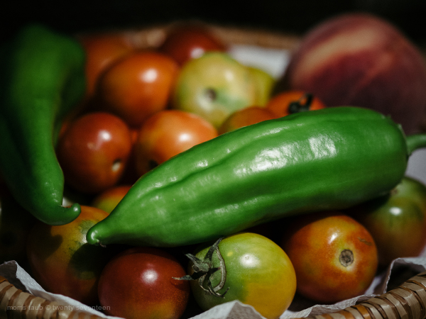 Basket of tomatoes, peppers with peach.