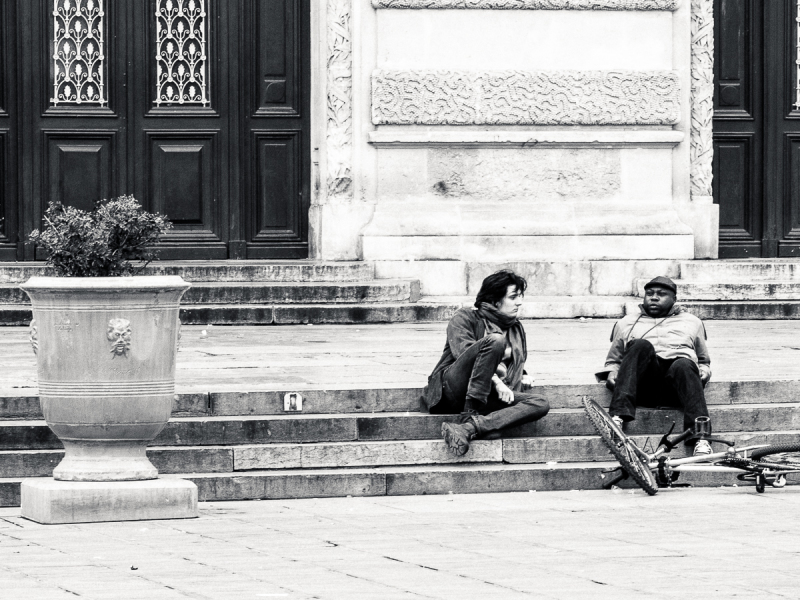 Two guys sitting on stairs.