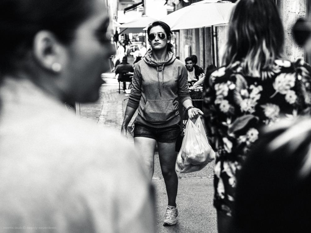 Woman walking carrying plastic bag. Street.