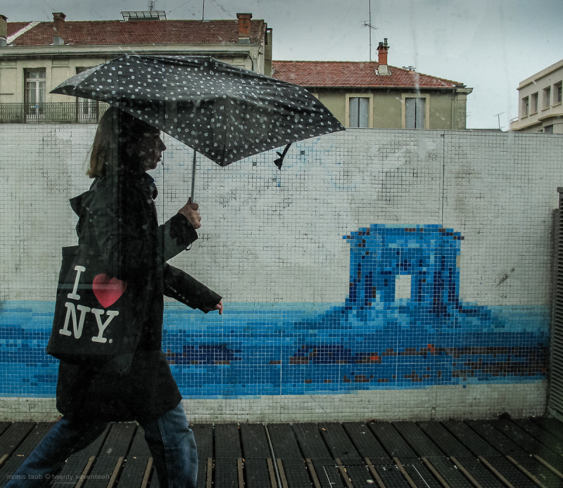 Woman in rain with I love NY bag.