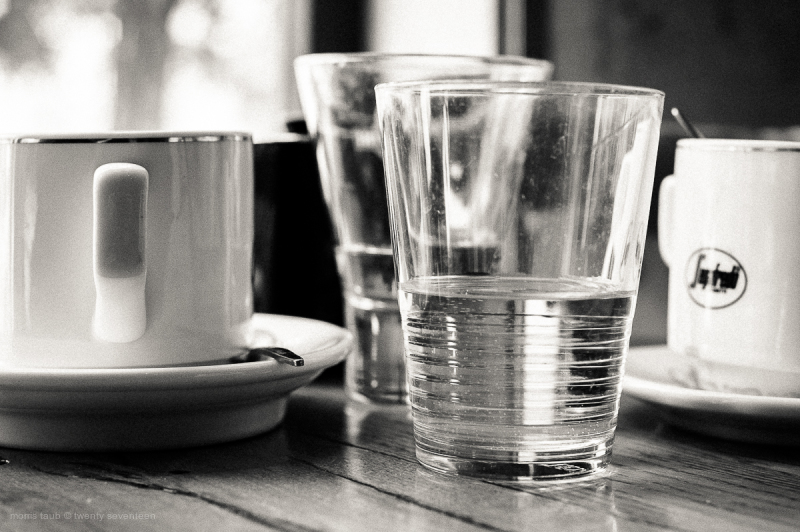 Coffee mugs and water glasses on cafe table.