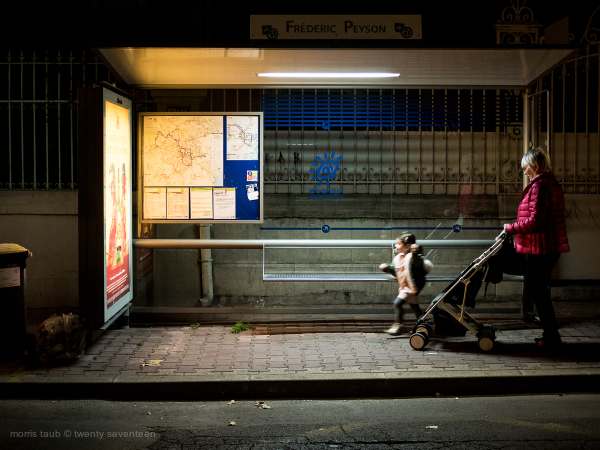 Woman and child at bus stop. Night.