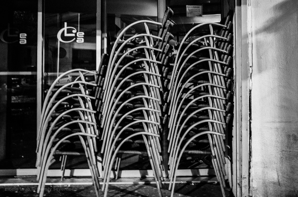 Bar chairs stacked at closing time.