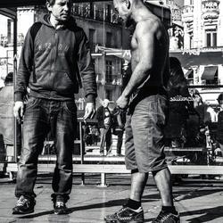 Two men one shirtless on tramway station.