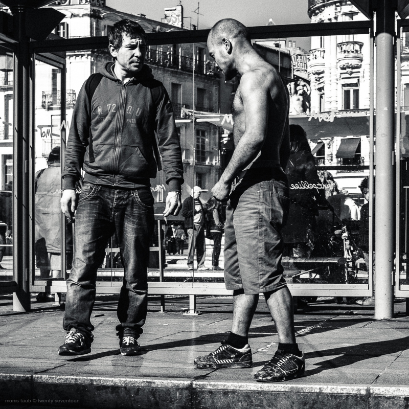 Two men one shirtless on tramway station.