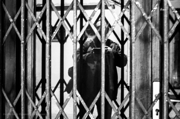 Self-portrait in store window with gates.