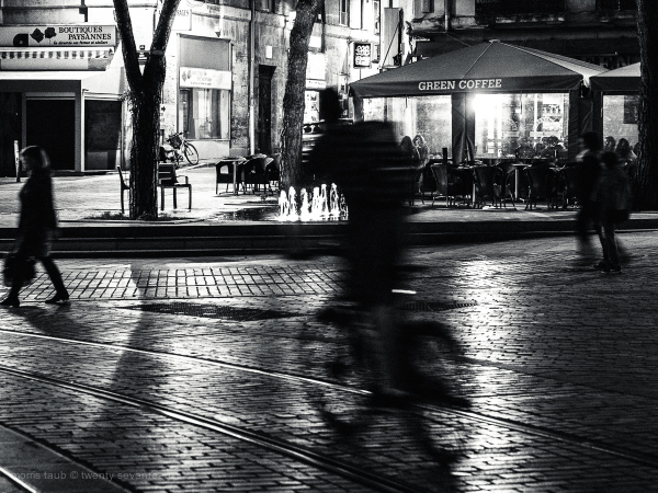 Biker and passersby at night at green coffee cafe.