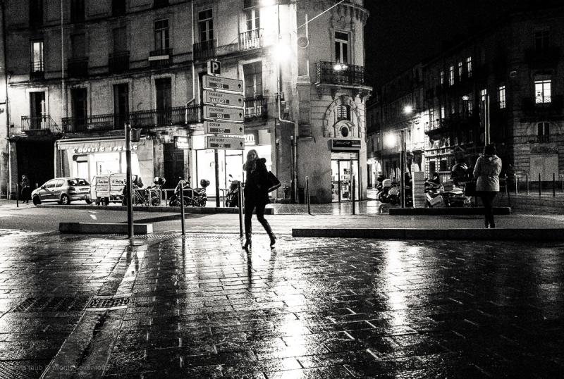 Woman walking on wet nightime street.