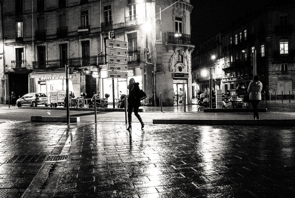 Woman walking on wet nightime street.