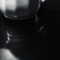 Portion of a milk pot on a cafe table.