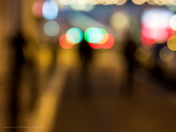 Three blurred figures walking the street. Night.