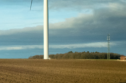 Part of wind turbine in a plowed field.