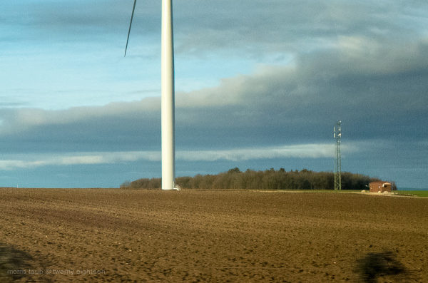 Part of wind turbine in a plowed field.