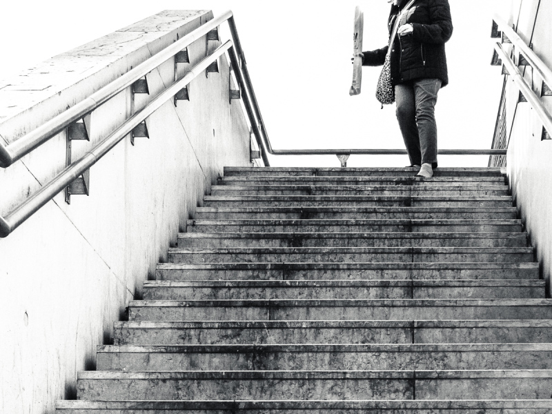 Woman descending stairs with baguette.